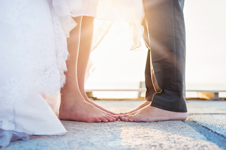 elegant dress: Feet of a bride and groom standing on the pier