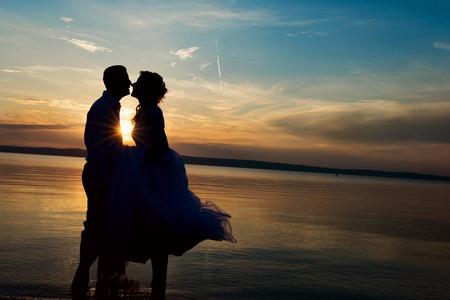 cielo y mar: pareja de boda joven hermosa que se coloca en la playa