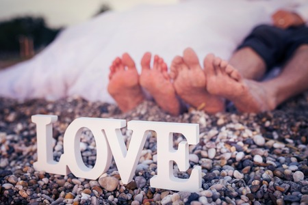 touching toes: Feet of a bride and groom sitting on a beach Stock Photo