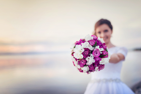 Mooie bruid met boeket staande op het strand