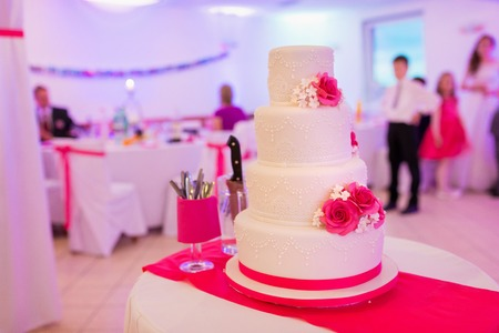 wedding chairs: A multi level white wedding cake laid on a table