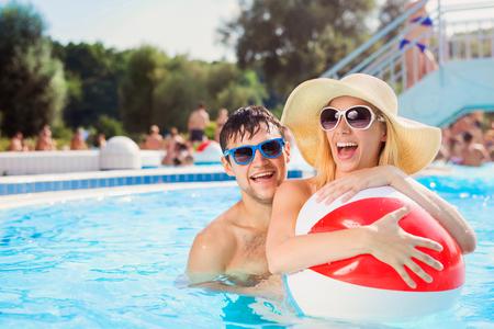 verano: Pareja joven hermosa que se divierte al aire libre en la piscina