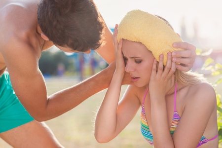 bikini couple: Young woman with heatstroke on a beach Stock Photo