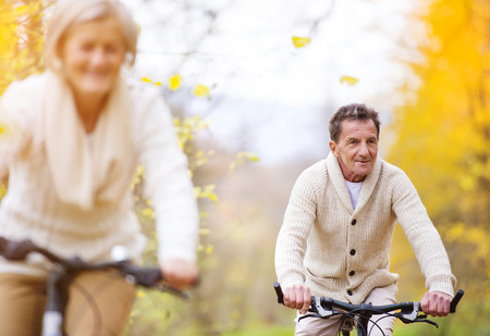 retirement happy man: Active seniors riding bikes in autumn nature. They having romantic time outdoor.