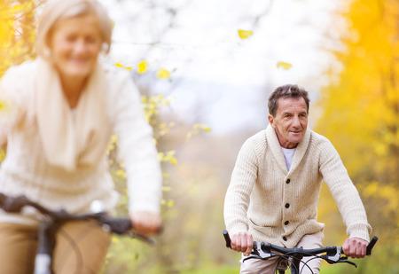 mariage: Les aînés actifs faire du vélo à l'automne la nature. Ils ayant romantique en plein air de temps. Banque d'images