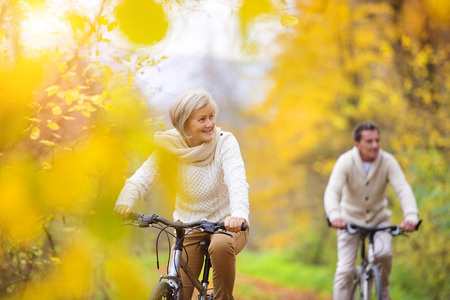 ancianos felices: Mayores activos andar en bicicleta en la naturaleza de otoño. Ellos tienen romántico tiempo al aire libre.