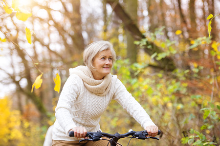 Active senior woman riding bike in autumn nature. They having romantic time outdoor. Stock Photo