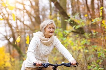 andando en bicicleta: Mujer mayor activo que monta en bicicleta en la naturaleza de otoño. Ellos tienen romántico tiempo al aire libre.