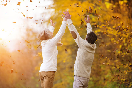 parejas caminando: Mayores activos divirti�ndose y jugando con las hojas en el oto�o de los bosques Foto de archivo