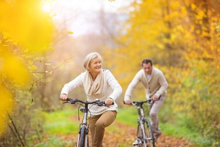 estilo de vida: S�niores ativos que montam bicicletas no outono natureza. Eles ter outdoor tempo rom�ntico.