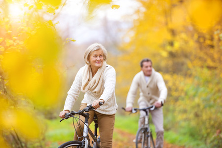 happy couple: Active seniors riding bikes in autumn nature. They having romantic time outdoor.