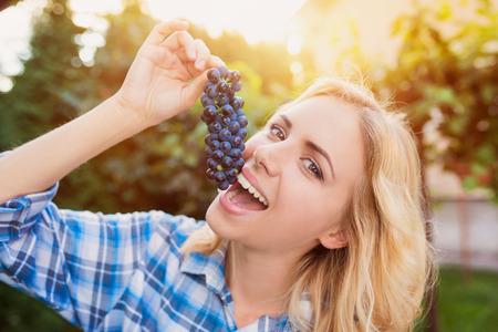 frutas divertidas: jóvenes hermosas uvas azules mujer rubia de cosecha