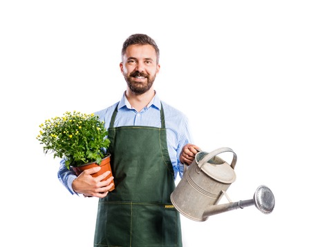 working man: Young handsome gardener in green apron. Studio shot on white background