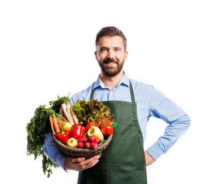 fruits in a basket: Young handsome gardener in green apron. Studio shot on white background