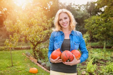 woman gardening: Beautiful young woman in denim shirt harvesting pumpkins