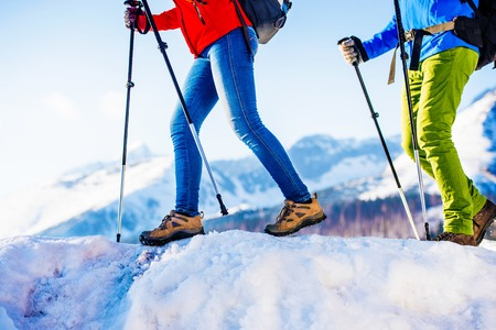 winter weather: Young couple hiking outside in sunny winter mountains Stock Photo