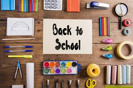 background color: Desk with stationary and with Back to school sign. Studio shot on wooden background. Stock Photo