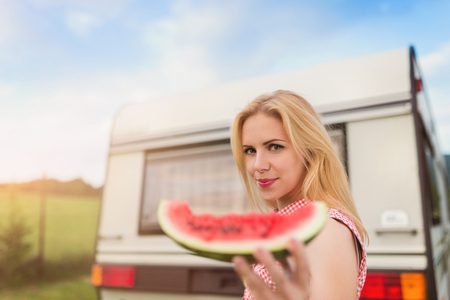 sky and grass: Beautiful young woman with a watermelon outside the camper van Stock Photo