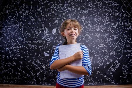 mignonne petite fille: Cute little girl in front of big blackboard Banque d'images
