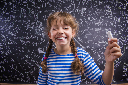 Cute little girl in front of big blackboard Фото со стока