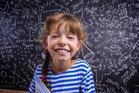 Cute little girl in front of big blackboard Stok Fotoğraf