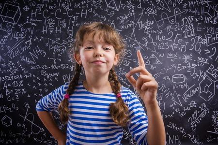 mignonne petite fille: Cute petite fille en face de grand tableau noir Banque d'images
