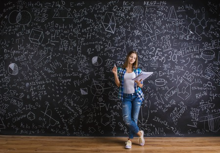 Beautiful young school girl in front of big blackboard