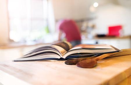 libros antiguos: Cocine libro sentado en una mesa de la cocina con dos cucharas de madera