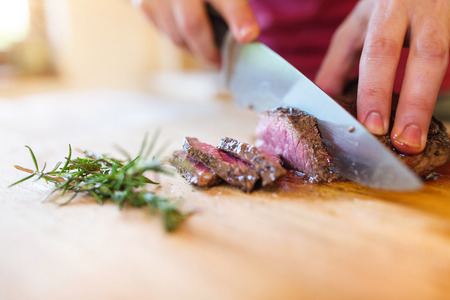 medium shot: Man slicing a grilled beef stead on a wooden cutting board Stock Photo