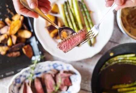 servings: Man serving grilled beef steak, asparagus and baked potatoes Stock Photo