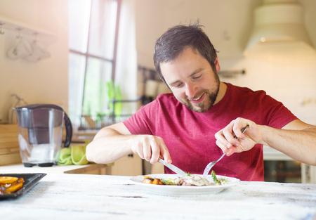 Irreconocible tenedor hombre celebración y un cuchillo cortar los alimentos en un plato
