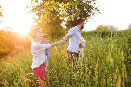 family in park: Happy young family having fun outside in spring nature Stock Photo