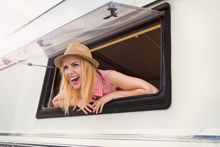 campervan: Beautiful young woman in a camper van on a summer day