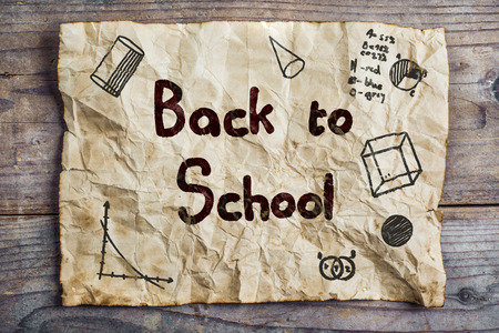 rumpled: Piece of old rumpled paper with Back to school sign on wooden floor background Stock Photo