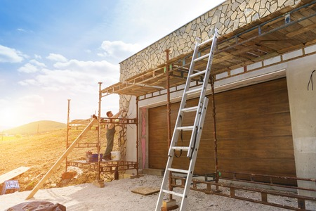 outside house: Mason putting decorative natural stones on a wall