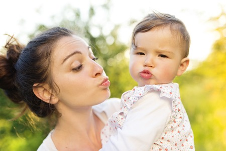 happy mom: Happy mother and her baby having fun outside in spring nature Stock Photo