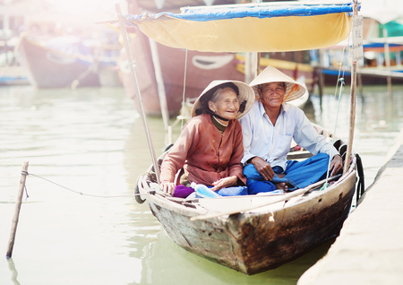 conical hat: Beautiful vietnamese senior couple in a traditional boat