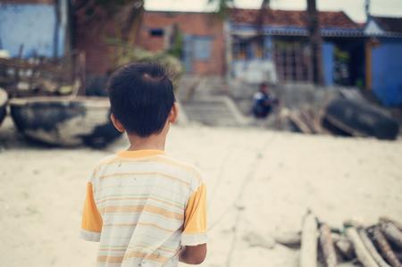 nam: Little vietnamese boy outside his house on a beach