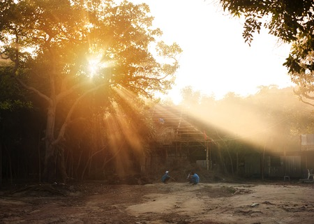 pobre: Niños vietnamitas que juegan fuera de su casa en la puesta de sol Foto de archivo