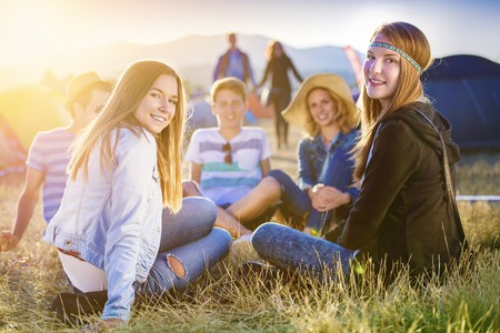 Group of beautiful teens camping at summer festival