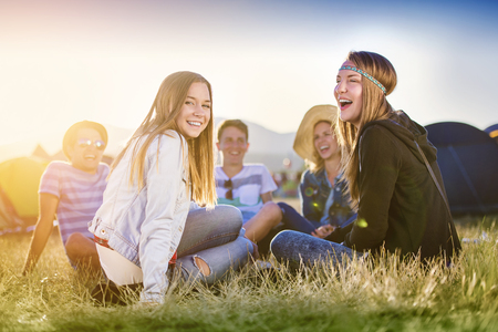happy teenagers: Group of beautiful teens camping at summer festival