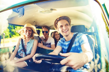 cars road: Beautiful young people on a road trip on a summers day Stock Photo