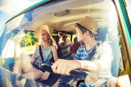 hombre manejando: Jóvenes hermosas en un viaje por carretera en un día de verano Foto de archivo