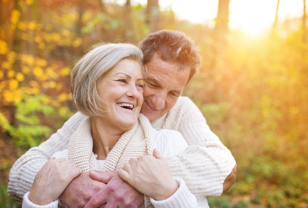 couple relaxing: Seniors in love on a walk in autumn forest