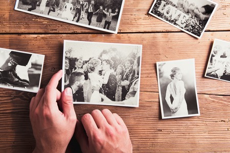 old picture: Wedding photos laid on a table. Studio shot on wooden background. Stock Photo