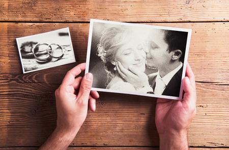 Fotos de la boda pusieron sobre una mesa. Estudio tirado en el fondo de madera. Foto de archivo - 45855799
