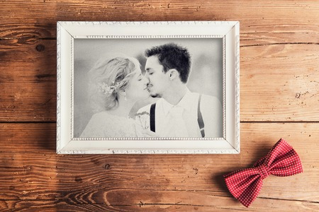 Picture frame with wedding photo. Studio shot on wooden background. Zdjęcie Seryjne
