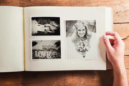フォト アルバムに新郎新婦の写真。木製の背景で撮影スタジオ。