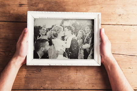 old hand: Picture frame with wedding photo. Studio shot on wooden background. Stock Photo