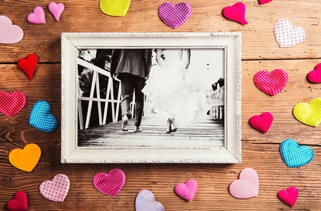 Picture frame with wedding photo. Studio shot on wooden background. Archivio Fotografico